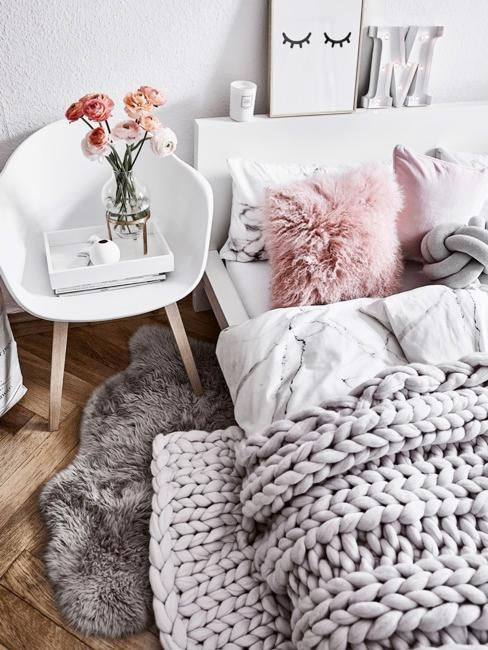 Letto con coperta grigia e cuscini rosa accanto a sedia bianca con vaso di fiori