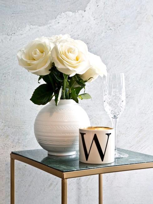 Bijzettafel met witte rozen in witte vaas en decoratie