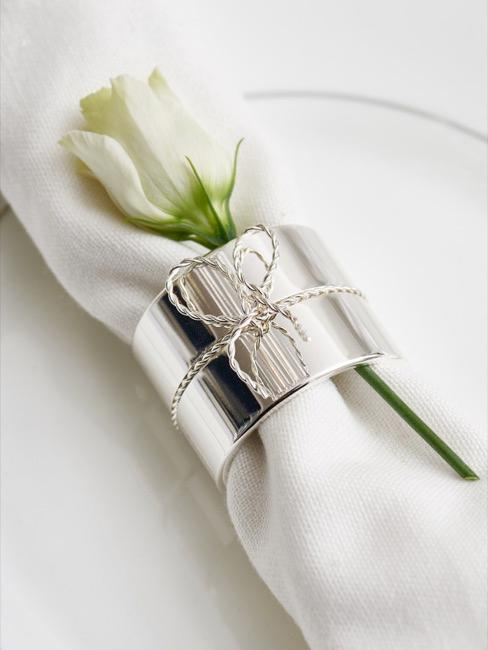 Close-up van een gedekte tafel met witte servet en zilveren servetring