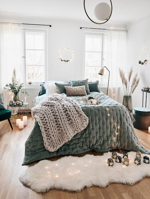 Łóżko z szałwiowo-zieloną narzutą i poduszkami, ozdobione beżowym kocem i jasnymi dodatkami