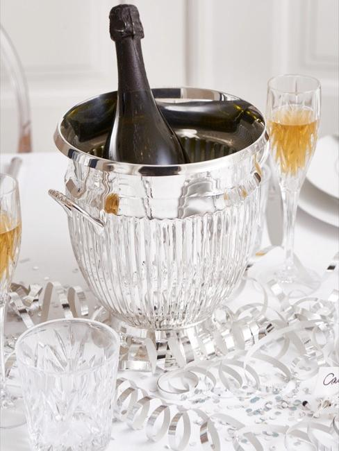 Close-up of champagne bottle in silver cooler on laid table
