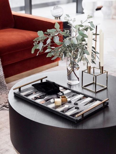 mesa de centro redonda con un florero y una bandeja decorativa, con sofá de color rojo óxido en el fondo