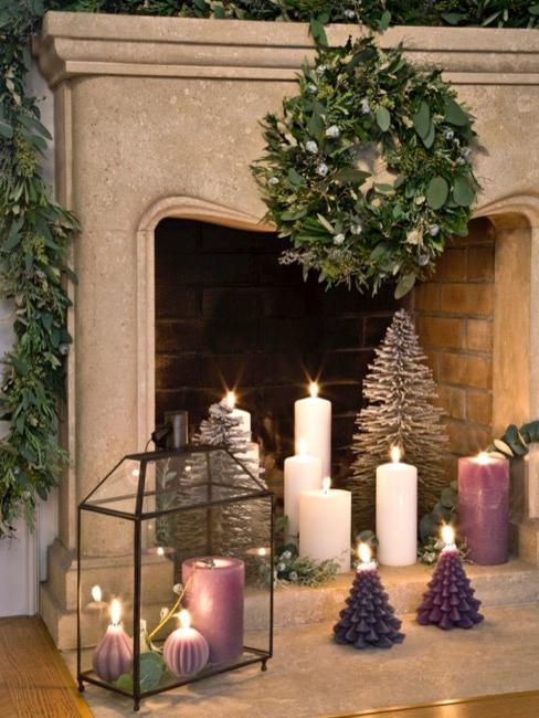 Nahaufnahme Kamin aus Stein mit weißen Kerzen und Tannenzweigen
