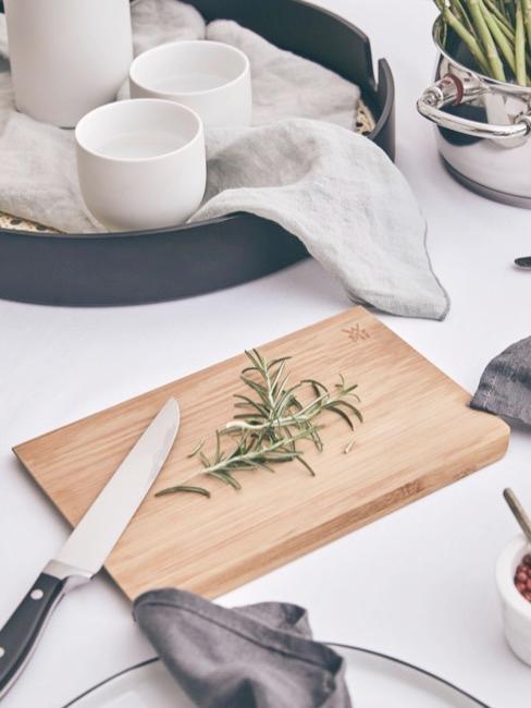 una tabla de cortar de madera, un cuchillo, una bandeja con vajilla blanca