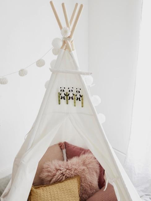Biały namiot typu tipi z poduszkami w środku