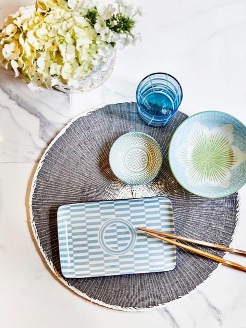 Dettaglio di piatti e ciotole in stile giapponese con bacchette e fiori