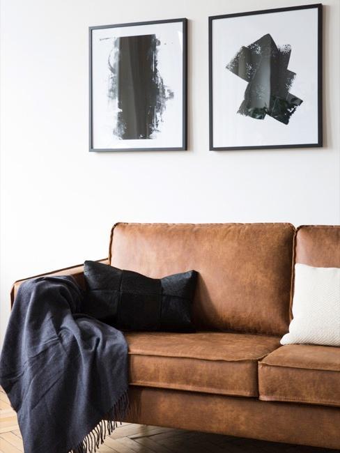 un sofá de cuero con una manta negra, cuadros en blanco y negro en la pared