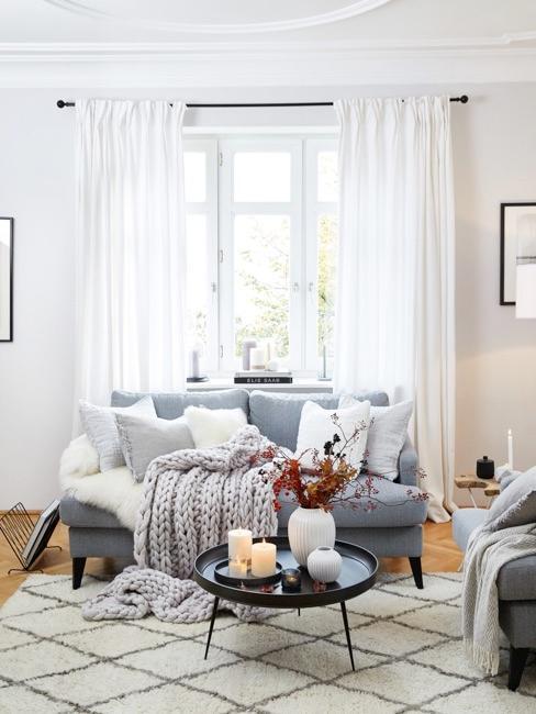 Woonkamer in oudblauw met witte gordijnen en kussens in wit en grijs
