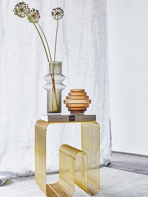 una mesa auxiliar dorada con jarrones decorativos de vidrio