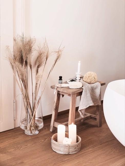 taburete pequeño con cosméticos y accesorios de baño, velas, jarrón decorativo