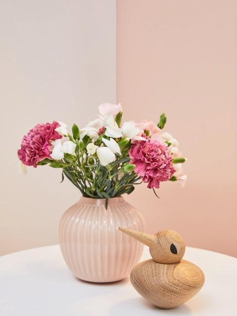 Bukiet kwiatów umieszczony w różowym wazonie na białym stole jadalnianym
