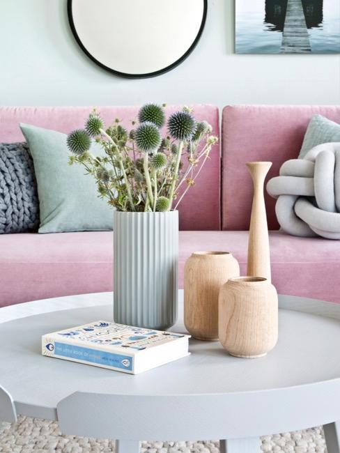salón con mesa de centro blanca, sofá de color rosa y accesorios de madera