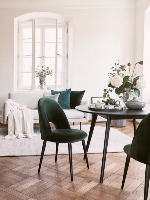 Soggiorno luminoso con divano grigio, tavolo rotondo nero e sedie nere