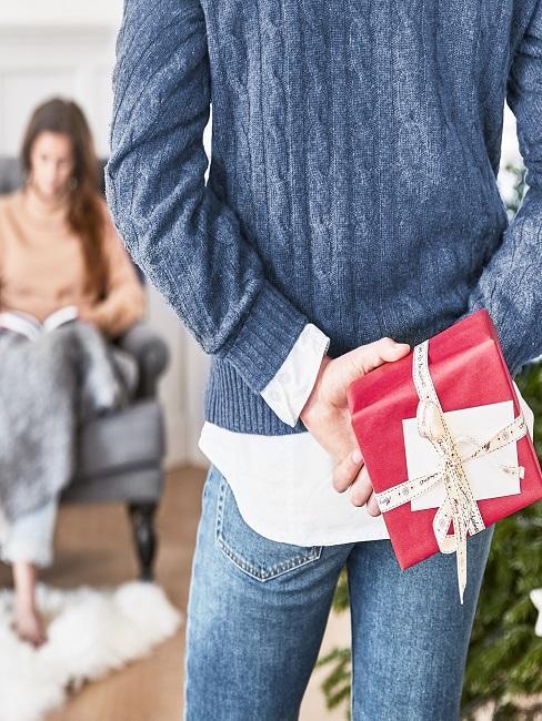 Mann hält Geschenk hinterm Rücken versteckt