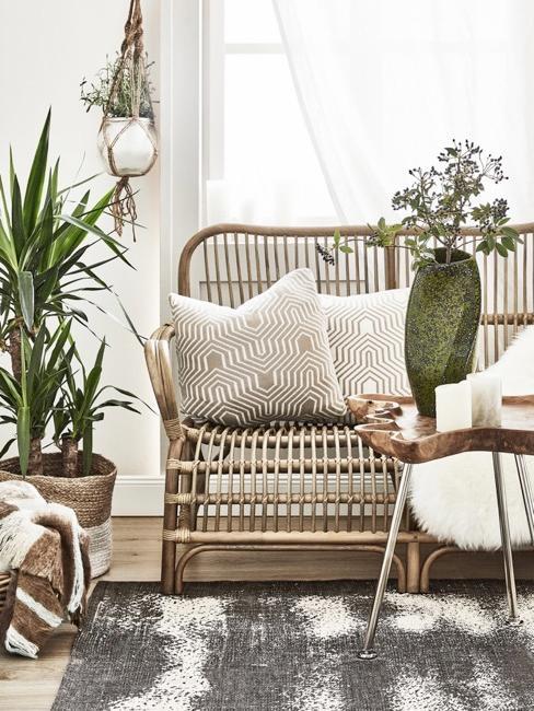Soggiorno con divano in rattan, cuscini bianchi e tappeto grigio