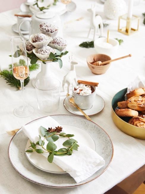 mesa blanca decorada con hojas verdes y vajilla blanca