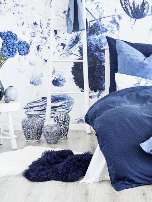 Dekoracja sypialni w kolorze niebiesko białym z kwiatową tapetą, kwiatami, wazonami i drabinką