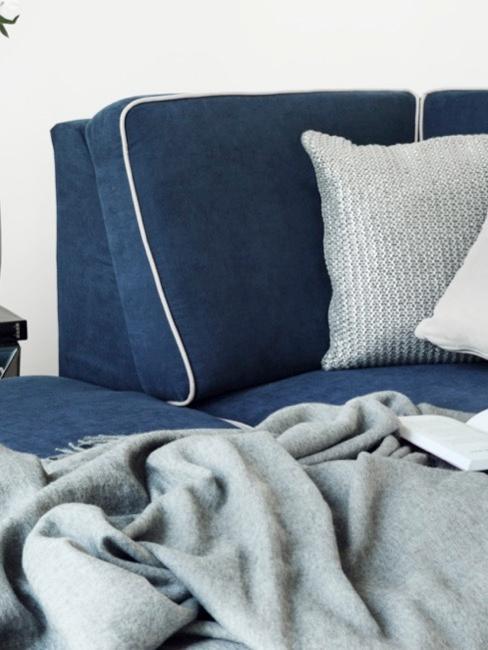 Tapicerowana sofa w kolorze granatowym z szarymi poduszkami i kocem