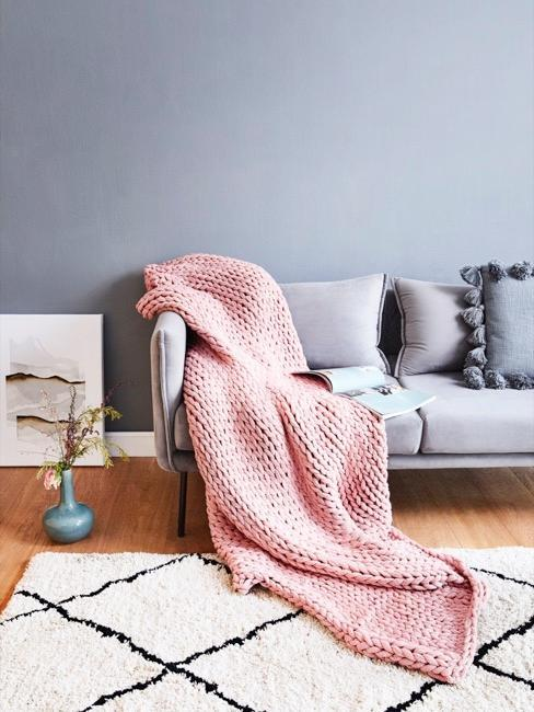 Salon zszaroniebieską ścianą, szarą sofą i różowym pledem