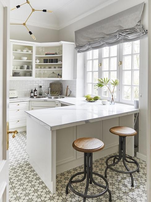 Weiße Küche mit Barhockern und Pendelleuchte