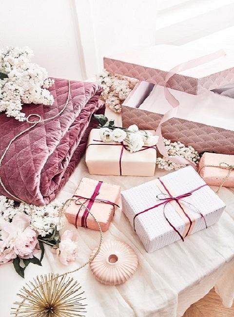 Prezenty z różowymi wstążkami oraz różowe pudełka prezentowe