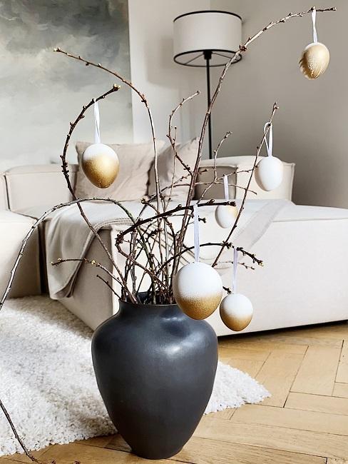 Vase mit Kirschblütenzweigen und Ostereiern