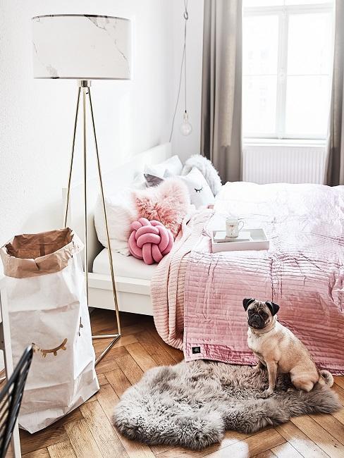 Pies siedzący na futerkowym dywanie w sypialni.