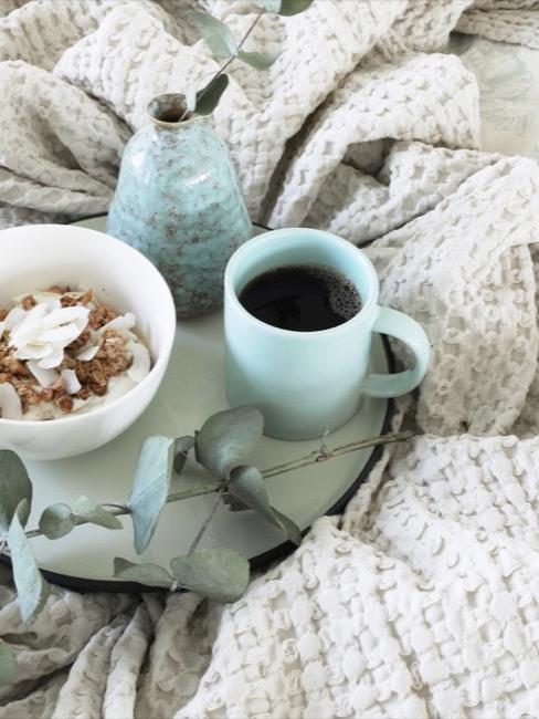 Nahaufnahme hellblaues Tablett mit Müslischale, Kaffetasse und Dekovase im cremfarbenen Bett
