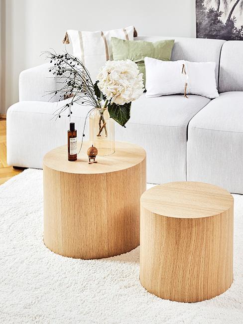 Okrągłe, drewniane stolik do kway z jasno szarą kanapą na beżowym dywanie