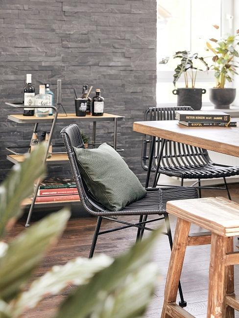 Zwei Stühle an einem Holztisch, im Hintergrund ein Servierwagen aus Holz und Metall sowie Pflanzendeko