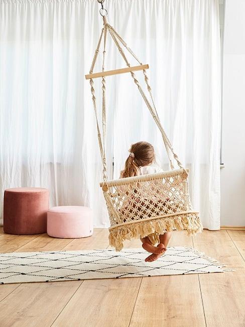 Ein Kind im Wohnzimmer von hinten auf einem Hängesessel