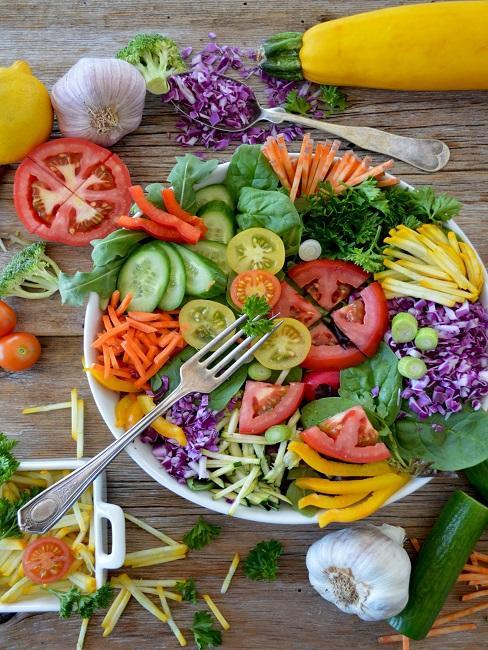 Salat auf einem Holztisch auf einem Teller und Außenrum
