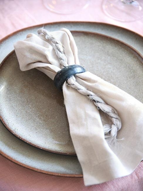 Zwei Teller übereinander auf einem gedeckten Tisch mit dekorativer Serviette
