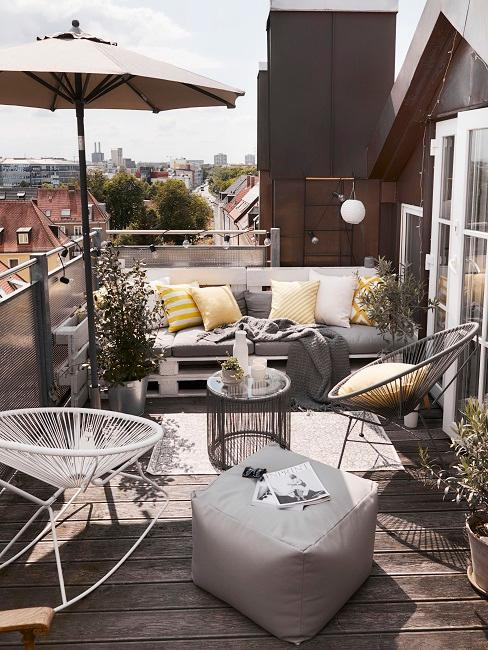 Sonnenschirm auf einer Terasse mit Pflanzen und Balkonmöbeln