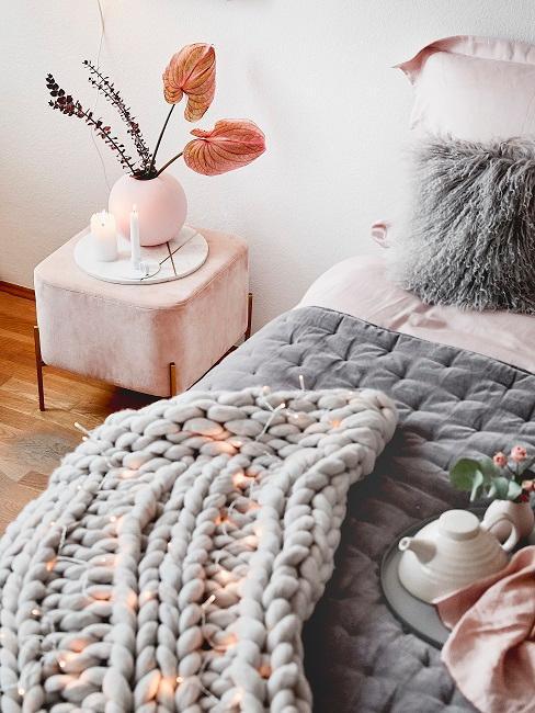Rosefarbene Callas in rosa Vase auf Nachtisch in Schlafzimmer