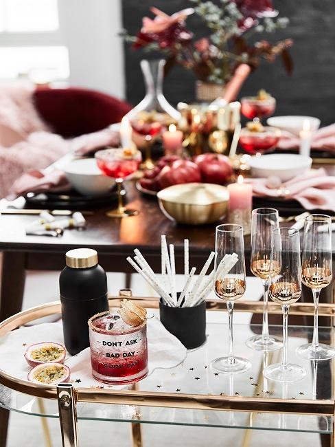 Wózek barowy z 4 kieliszkami do szampana i zastawionym stołem w tle.