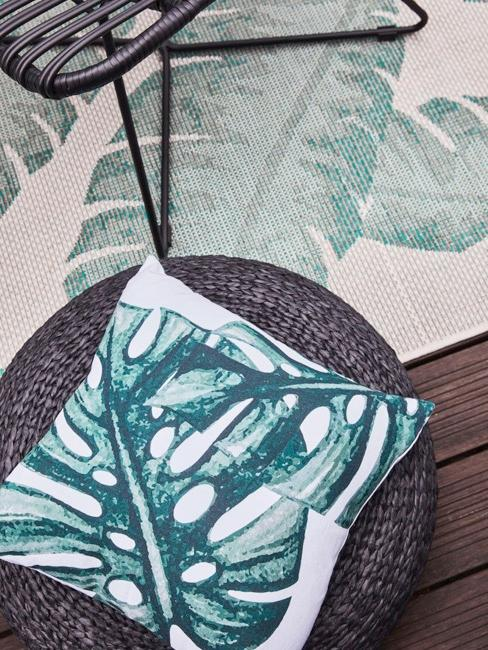 Cushions with Monstera leaf on poug on terrace