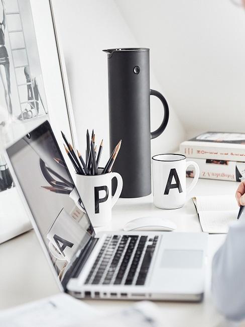 Laptop auf einem Schreibtisch, daneben Stifte, Bücher & Co. und eine Isolierkanne