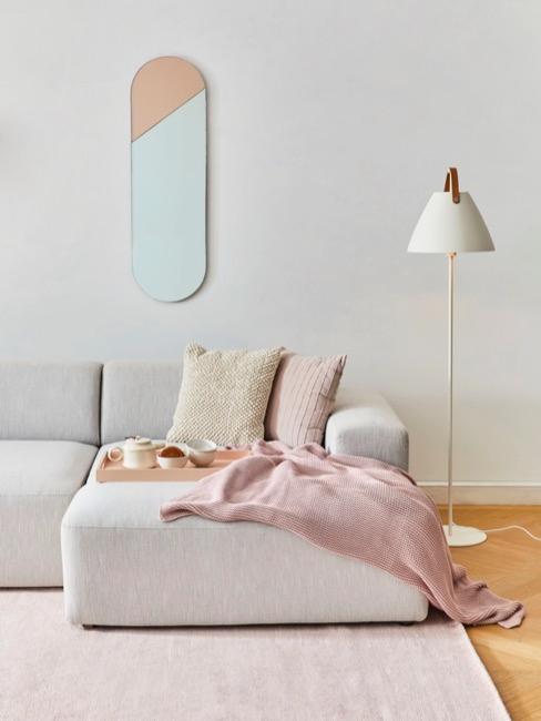 Salotto in stile scandinavo hygge con divano grigio e accenti color pastello