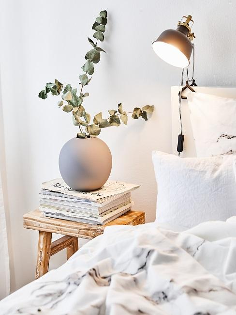 Eukalyptus in einer runden Vase auf dem Nachtkästchen