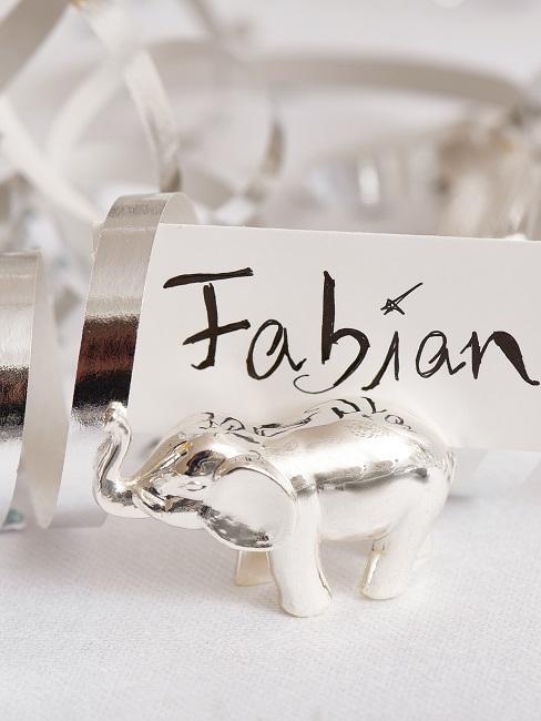 Ein kleiner Deko Elefant auf einer Tafel vor einer Tischkarte mit dem Namen Fabian