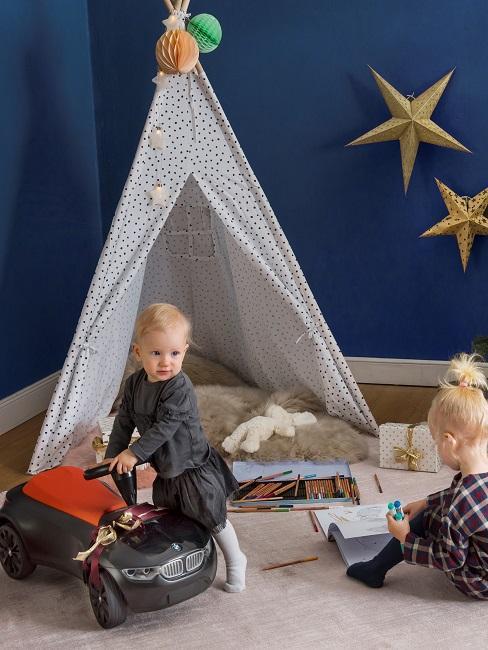Dwoje dzieci bawiących się obok namiotu w pokoju dziecięcym