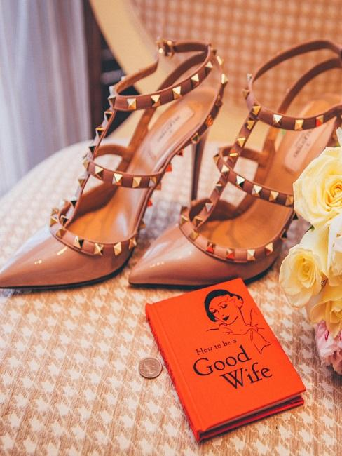 zapatos de diseño con un libro naranja  how to be a good wife