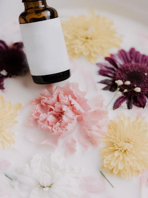 KLeines Fläschchen mit Naturkosmetik über einem Blütenbad