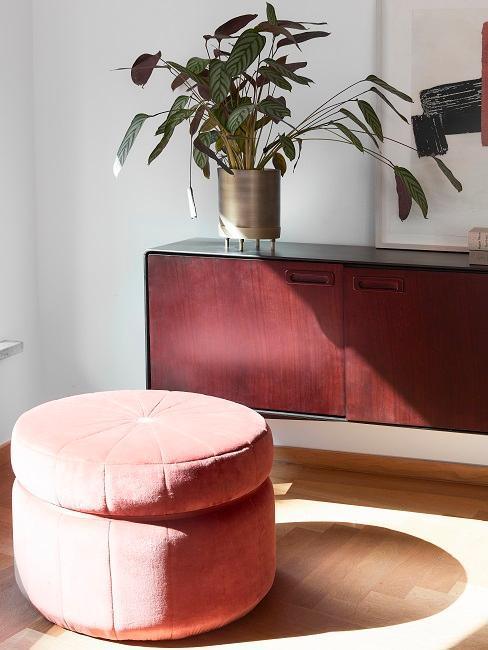 Ein Pouf steht neben einem Sideboard mit einer Toppflanze darauf in einem goldenen Topf