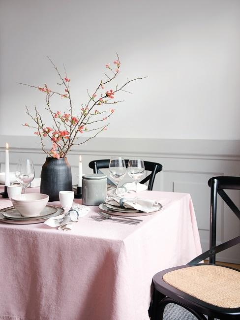 Tavola con tovaglia rosa e vaso con fiori di ciliegio