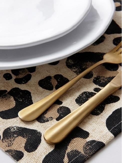 Bieżnik w nadruk w panterkę oraz złote sztućce i biała zastawa stołowa