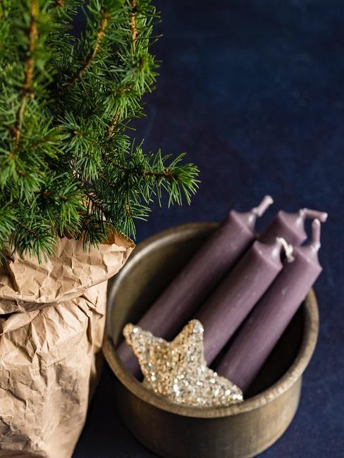 Schale mit Kerzen und Stern neben Weihnachtsbaum