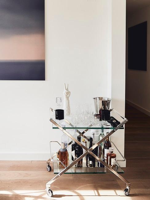 Carrello bar con bicchieri di cristallo, candele decorative e decanter