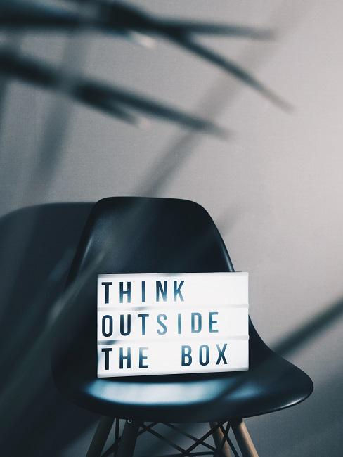 "Lightbox ""Think outside the box"" auf einem Stuhl"